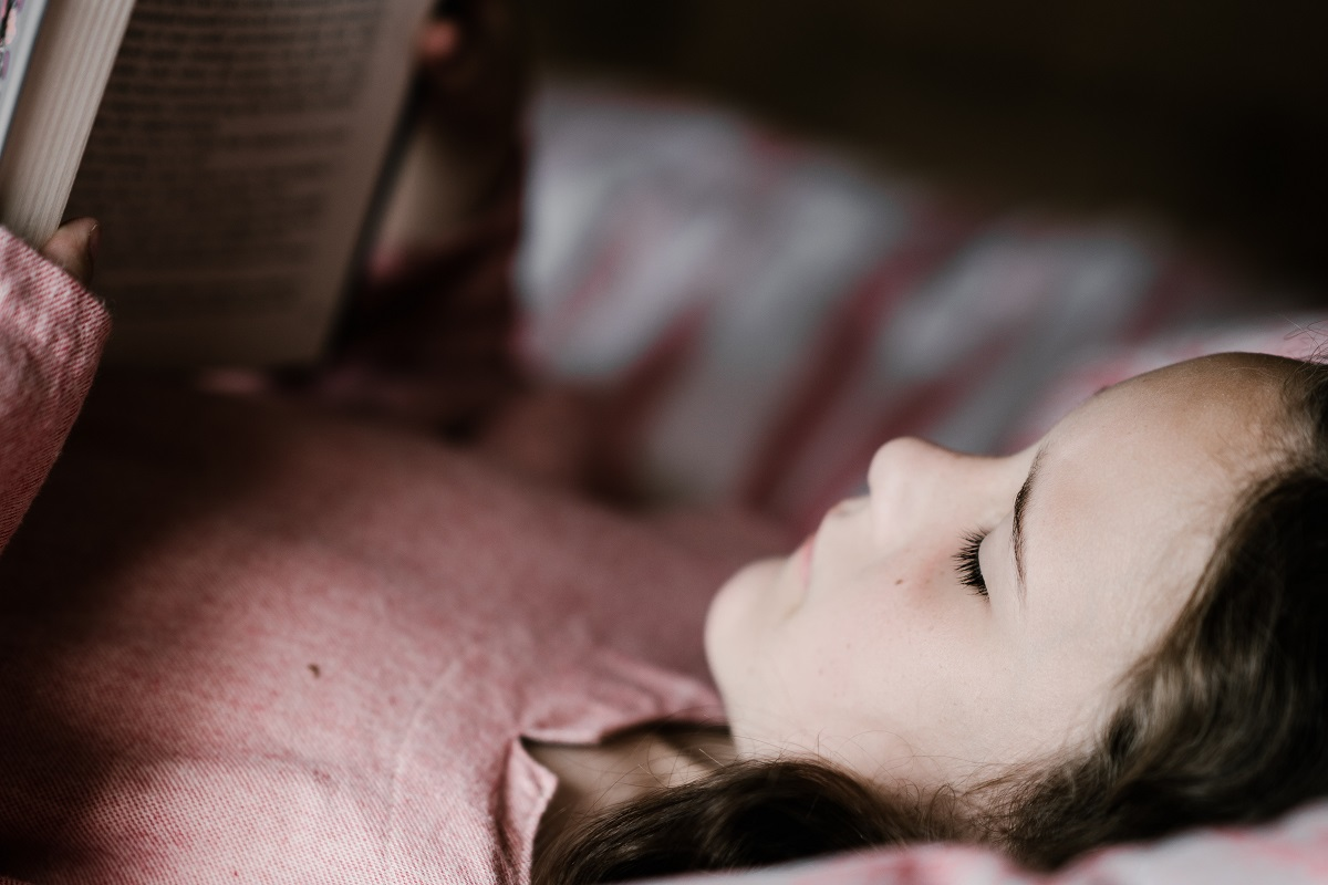 Una bambina sta leggendo un libro per bambini