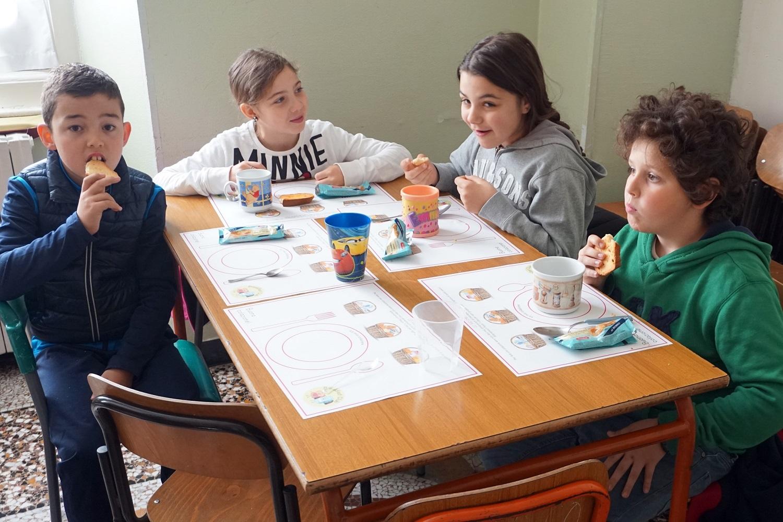 Dei bambini seduto al banco fanno colazione