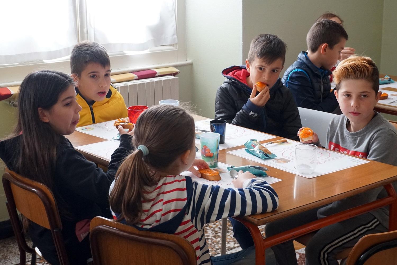 Dei bambini parlano e fanno colazione