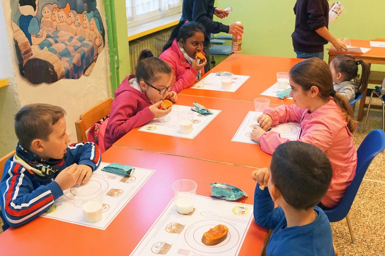 Dei bambini mangiano pane e marmellata.
