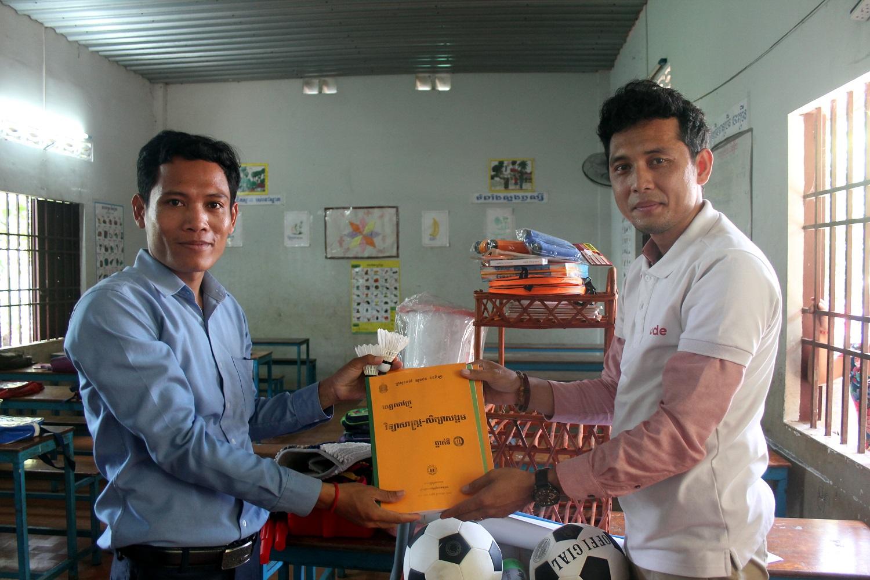 La consegna del materiale scolastico a un insegnante cambogiano