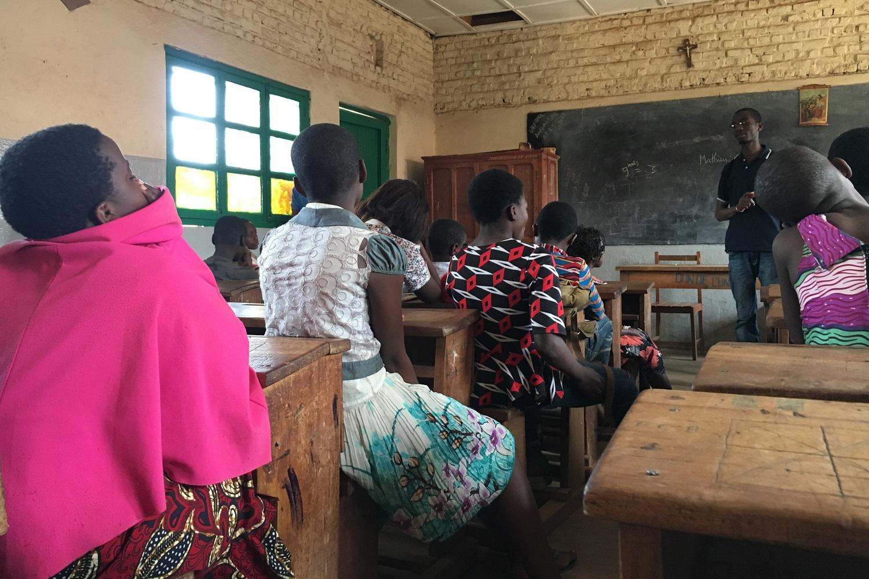 Dei bambini seduti al banco ascolta la spiegazione del loro professore