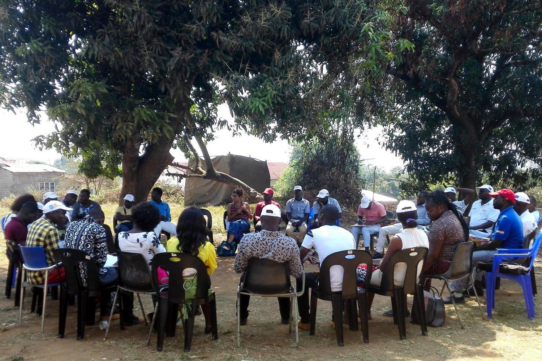 Un gruppo di persone seduto in cerchio, all'aperto