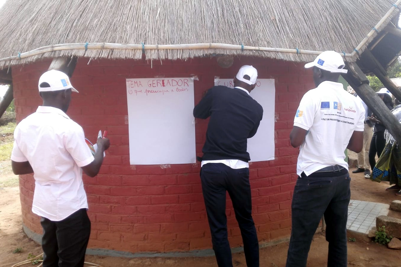 Delle persone scrivono su dei fogli attaccate a un muro