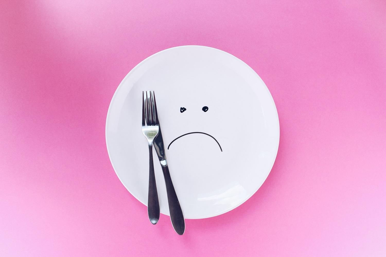 un piatto vuoto con una faccia triste disegnata a testimonianza di denutrizione e malnutrizione