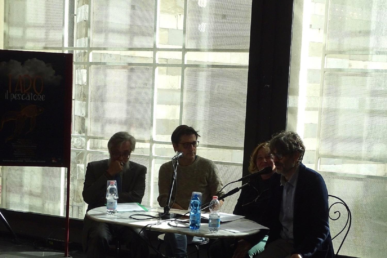Alcune persone a un tavolo durante una conferenza stampa