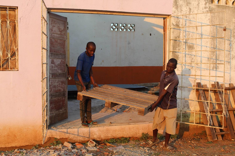 Due uomini portano fuori un asse di legno da un edificio da ristru