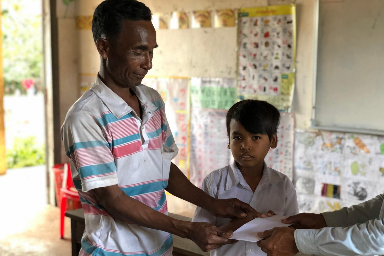 Un padre cambogiano e suo figlio ricevono una borsa di studio.