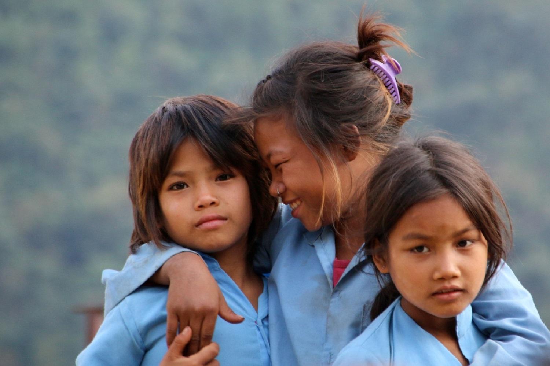 Tre studentesse nepalesi sorridono alla macchina fotografica