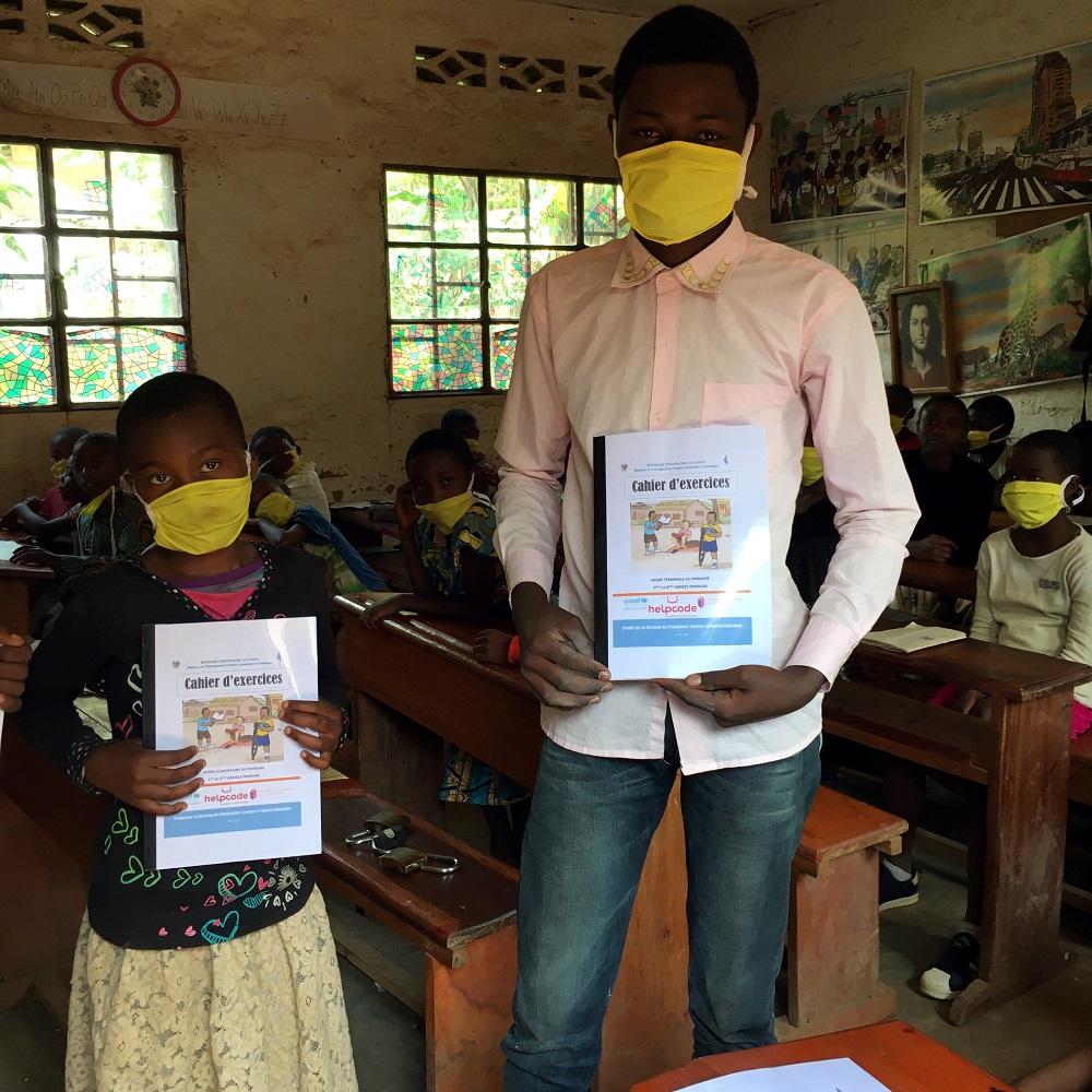 Studenti congolesi mostrano i loro libri di esercizi
