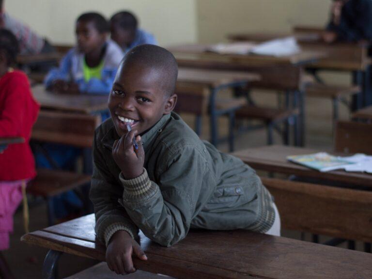 Un bambino mozambicano sorride al banco