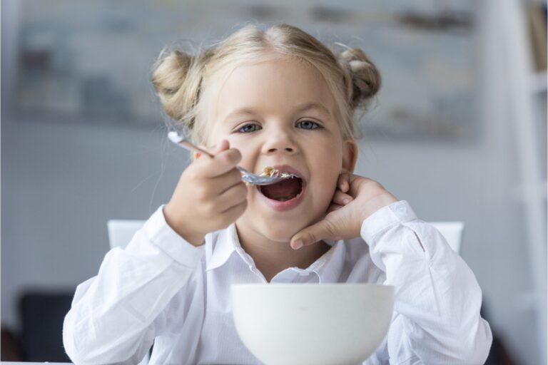 Una bambina fa colazione