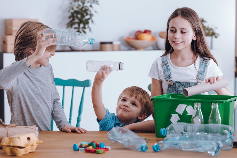 Dei bambini si divertono a riciclare delle bottiglie di plastica