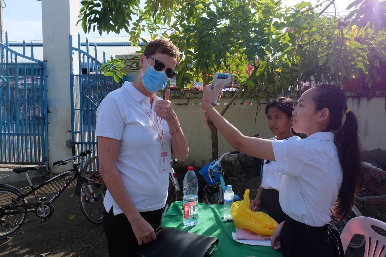 Una studentessa misura la temperatura a una persona in visita